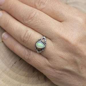 Silver ring with opal gemstone caboshon on female hand
